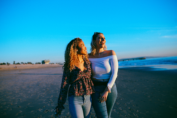 young female friends enjoying the walk on the Venice beach in LA, California Photograph by Lechatnoir