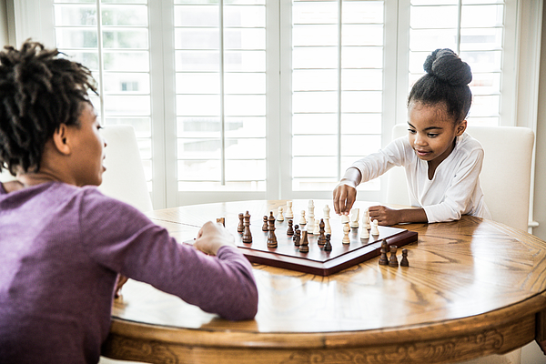 Young girl (6yrs) playing chess with mother Photograph by MoMo Productions