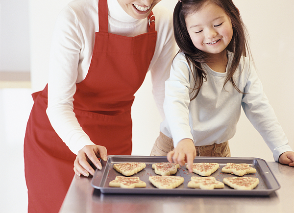 Young Girl Stands With Her Mum By The Kitchen Counter, Choosing A Christmas Cookie From A Baking Tray Photograph by Digital Vision.
