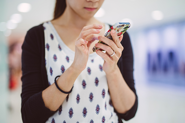 Young lady using smartphone in mall Photograph by Images By Tang Ming Tung