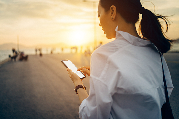 Young lady using smartphone while having a relaxing walk by the pier afterwork at sunset Photograph by D3sign