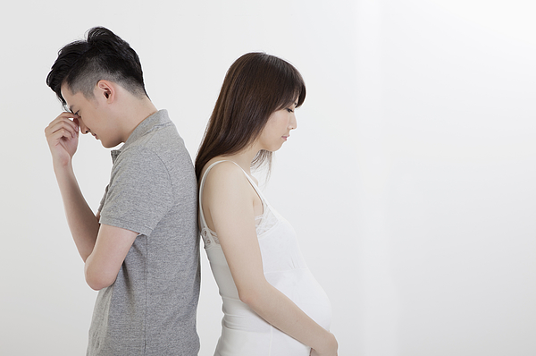 Young man and pregnant woman standing with back to back, Photograph by IMAGEMORE Co, Ltd.