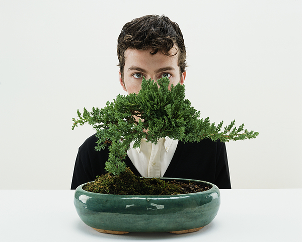 Young man behind bonsai tree, portrait Photograph by Digital Vision