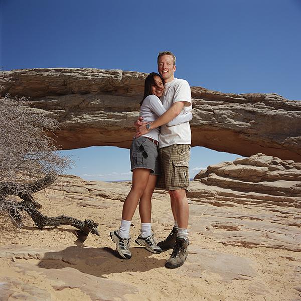 Young Man Checkered Shorts T-shirt Hugs Young Woman In Gray Shorts White Shirt At A Natural Arch Photograph by Photodisc