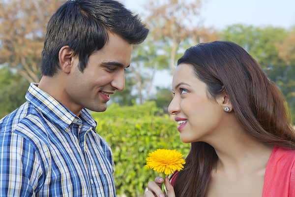 Young man giving a flower to a young woman Photograph by IndiaPix/IndiaPicture