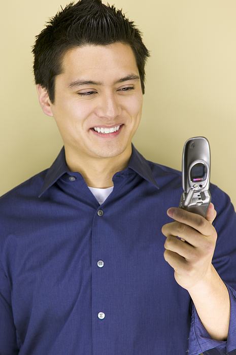 Young man looking at a mobile phone Photograph by Photodisc