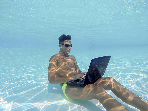 Young man using computer underwater Photograph by PJPhoto69