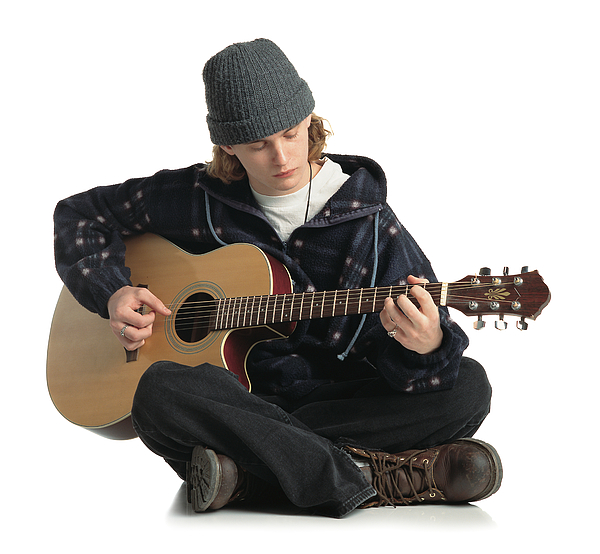 Young Man Wearing A Gray Hat Jacket And Dark Pants Sits On The Ground While Playing A Guitar Photograph by Photodisc