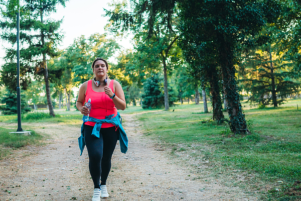 Young overweight woman running Photograph by Urbazon