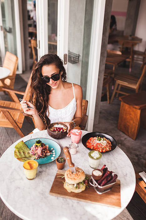 Young smiling woman having breakfast in stylish street cafe. Smoothie bowl, matcha latte, tacos and burger Photograph by Olegbreslavtsev