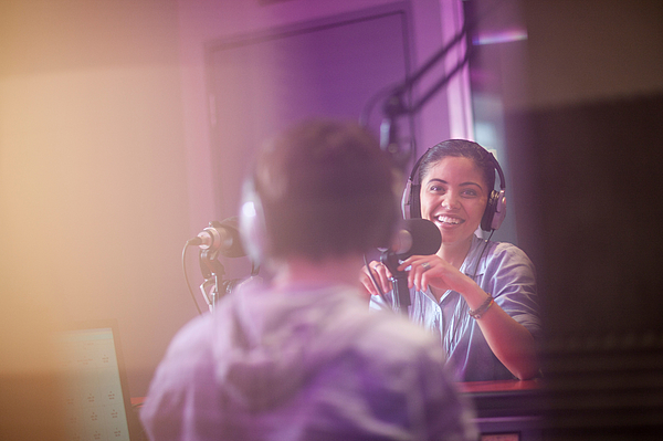 Young woman and man broadcasting in recording studio Photograph by Zero Creatives