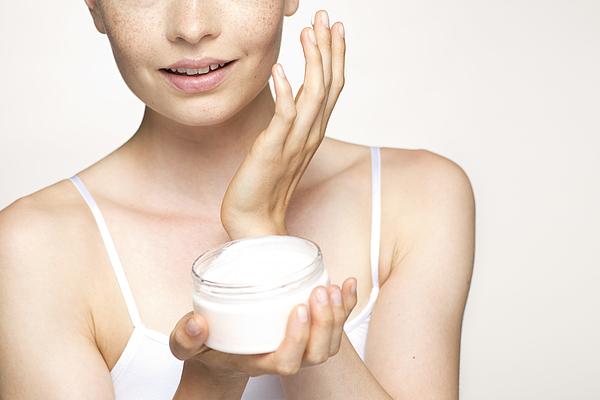 Young woman applying moisturizer to face, portrait Photograph by PhotoAlto/Milena Boniek