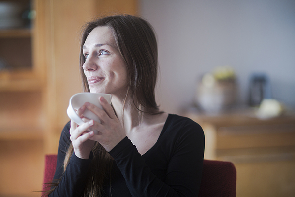Young woman at home, holding hot drink Photograph by Sigrid Gombert