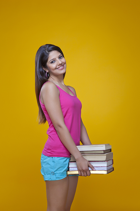 Young woman carrying a pile of books Photograph by Ravi Ranjan