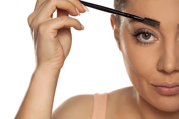 Young woman contouring her eyebrows with dry brush on white background Photograph by VladimirFLoyd