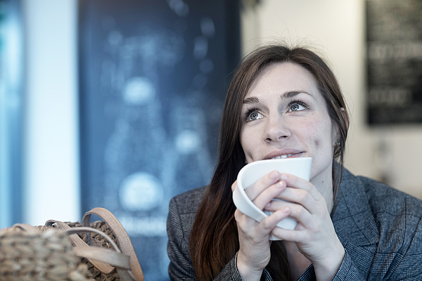 Young woman drinking coffee in cafe looking up Photograph by Sigrid Gombert