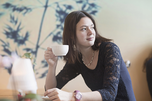 Young woman drinking coffee in coffee shop, Freiburg Im Breisgau, Baden-Württemberg, Germany Photograph by Sigrid Gombert