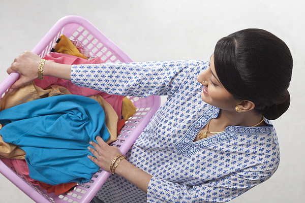 Young woman holding a basket of clothes Photograph by Hemant Mehta