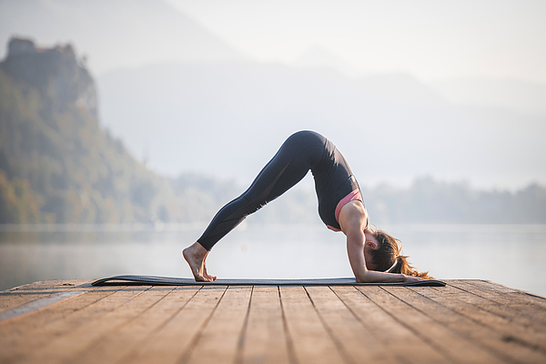 Young Woman in Dolphin Pose on Pier Overlooking Lake Bled Photograph by AzmanL