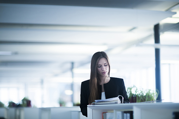 Young woman in office looking down at paperwork in ringbinder file Photograph by Sigrid Gombert