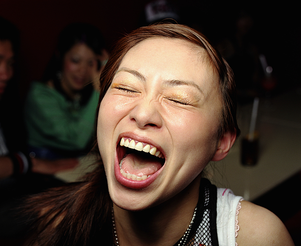 Young woman laughing, eyes closed, close-up Photograph by Ryan McVay