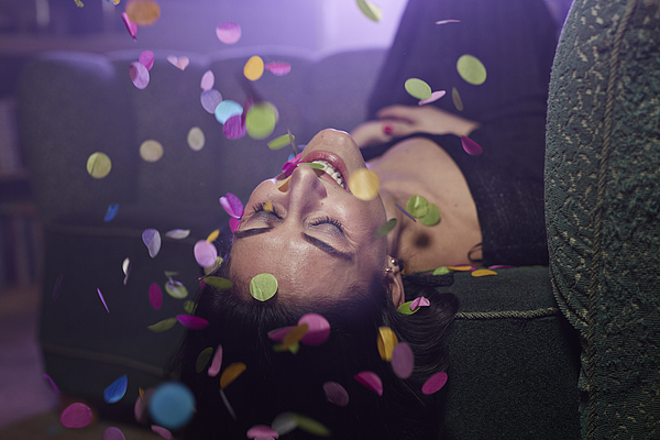 Young woman laying on sofa with confetti falling Photograph by Klaus Vedfelt