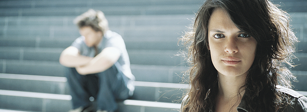 Young woman looking at camera, young man sitting in background Photograph by Matthieu Spohn