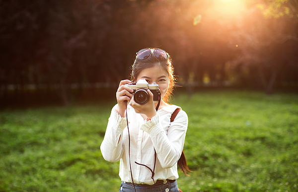 Young woman taking photograph with camera against sunset Photograph by Xia Yuan