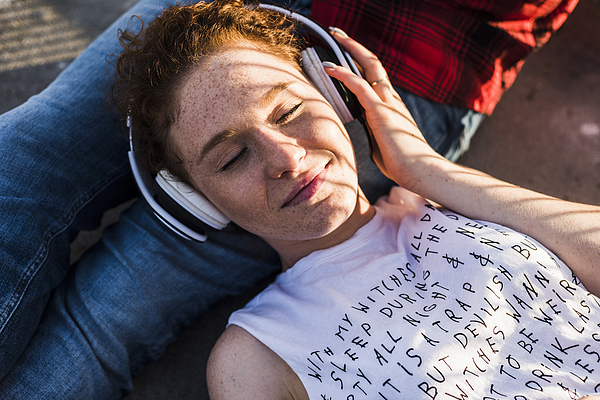 Young woman with headphones lying on boyfriends lap Photograph by Westend61
