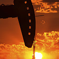 Oil Rig Pump Jack Silhouetted By Setting Sun by Mark Duffy