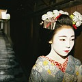 A Geisha In Traditional Costume Walks by Paul Chesley