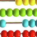 Closeup Of Bright  Abacus Beads On White by Sandra Cunningham