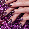 Closeup Of Woman Hands With Purple Nail Polish by Maxim Images Prints