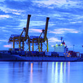 Container Cargo Freight Ship With Working Crane Bridge In Shipya by Anek Suwannaphoom
