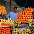 Market Vendor Selling Fruit In A Bazaar by Sami Sarkis