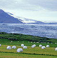 Meadow With Hay Bales And Glaciers Near Jokulsarlon Lagoon In Iceland by Sami Sarkis