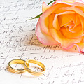 Rose And Two Rings Over Handwritten Letter by U Schade