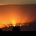 Setting Sun Peaking Out From Storm Clouds In Saskatchewan by Mark Duffy
