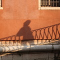 Shadow Of A Person Crossing The Shadow Of A Bridge In Venice by Michael Henderson