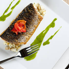 GREY MULLET WITH WATERCRESS SAUCE presented on a square white plate with cutlery and napkin by Andy Smy