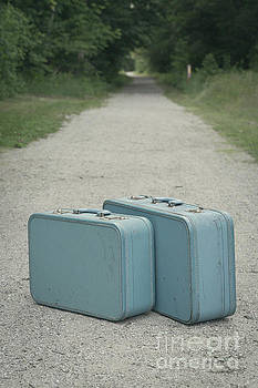 Edward Fielding - Vintage blue suitcases on a gravel road