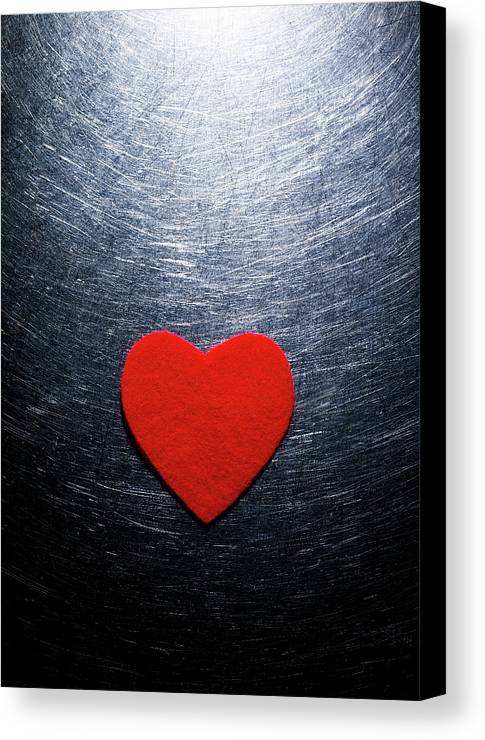 Vertical Canvas Print featuring the photograph Red Felt Heart On Stainless Steel Background. by Ballyscanlon