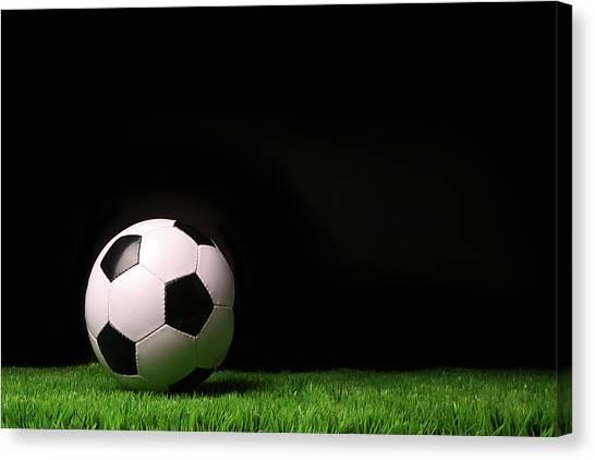 Soccer Ball On Grass Against Black Canvas Print