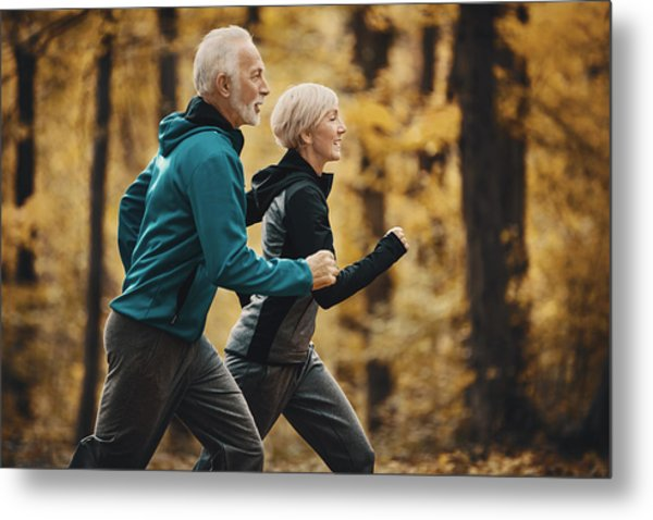 Senior Couple Jogging In A Forest. Metal Print by Gilaxia
