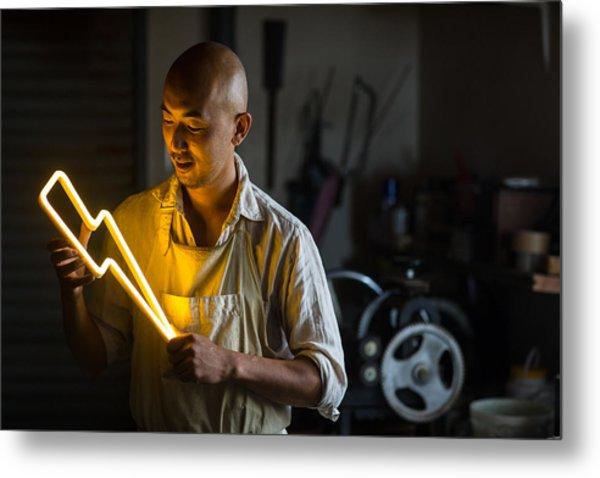 Craftsmen Holding A Lightning Bolt Shaped Neon Light Metal Print by Trevor Williams