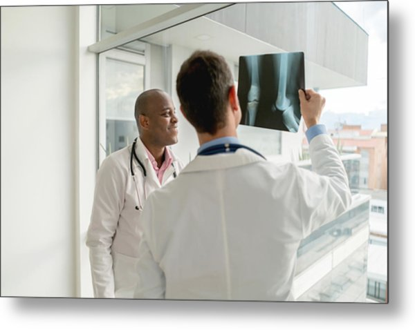 Doctors Looking At An X-ray Metal Print by Andresr