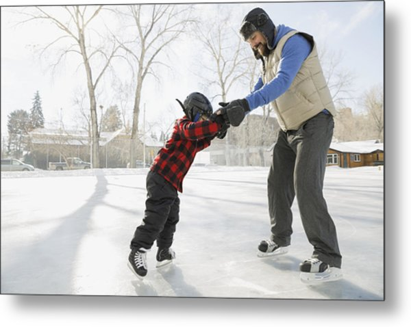 Father Teaching Son To Ice-skate On Outdoor Rink Metal Print by Hero Images