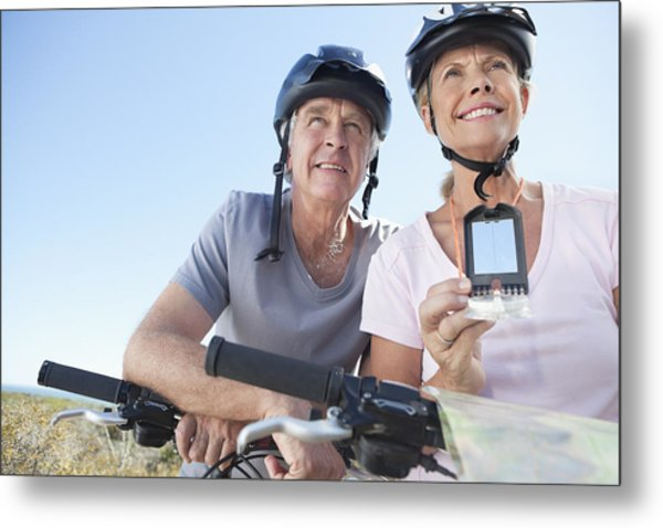 Happy Mature Woman Mountain Biking With Man Using Gps Metal Print by OJO Images