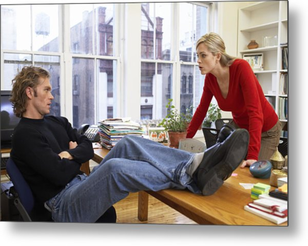Male Office Worker With Feet On Desk, Woman Leaning On Edge Of Desk Metal Print by Christopher Robbins