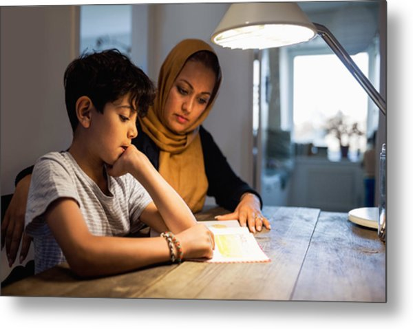Mother And Son Reading Book Under Illuminated Desk Lamp At Home Metal Print by Maskot